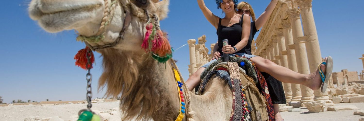 two girls are ride on camel in desert