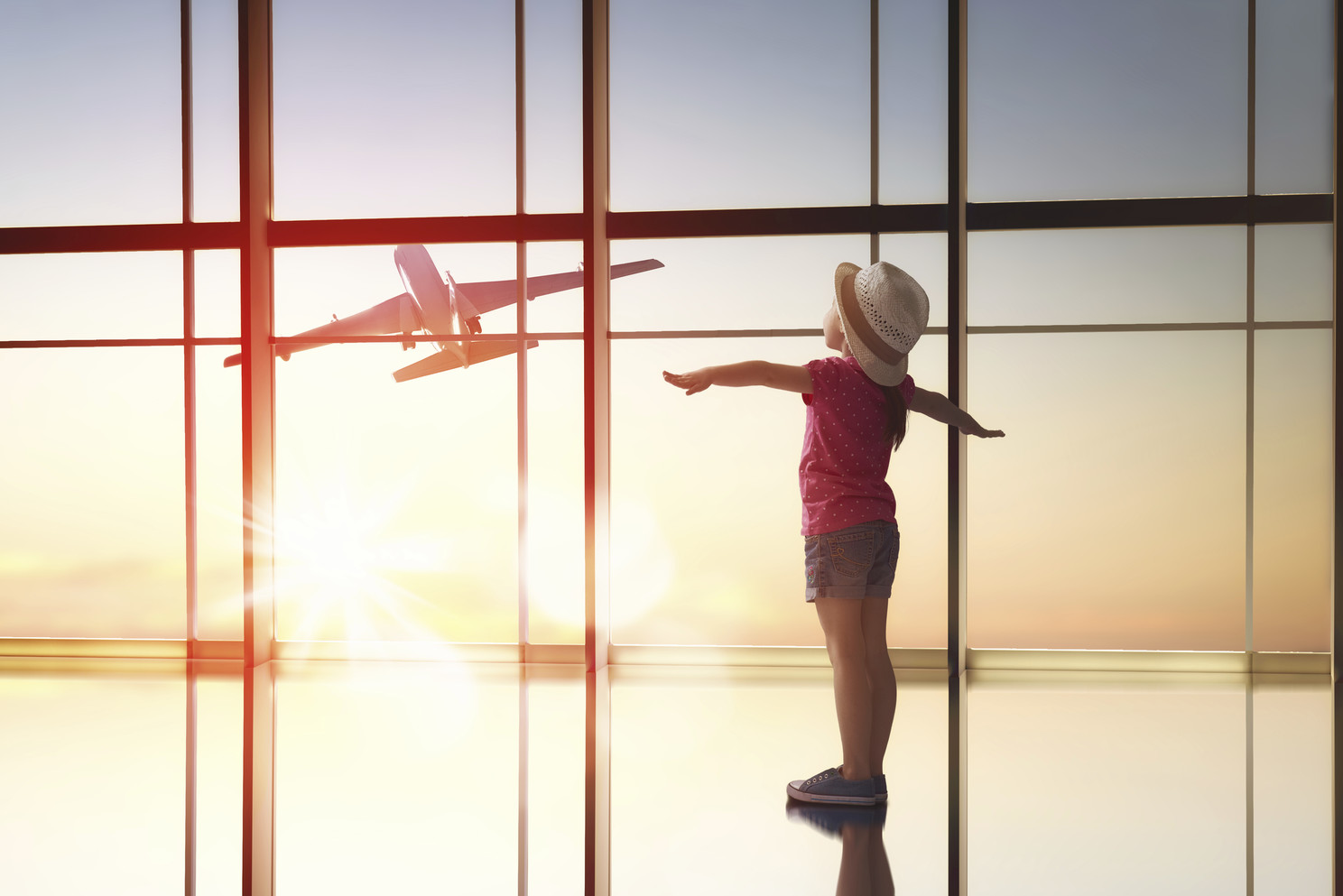 girl looks at a plane at the airport